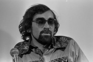 Man with dark curly hair and beard wearing aviator sunglasses and print shirt behind silver microphone